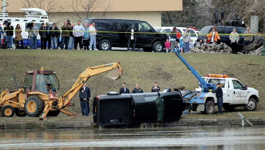 A black pickup truck is removed from the water Friday morning near 123rd Street in Troy. (Skip Dickstein / Times Union) Photo: SKIP DICKSTEIN / 2008