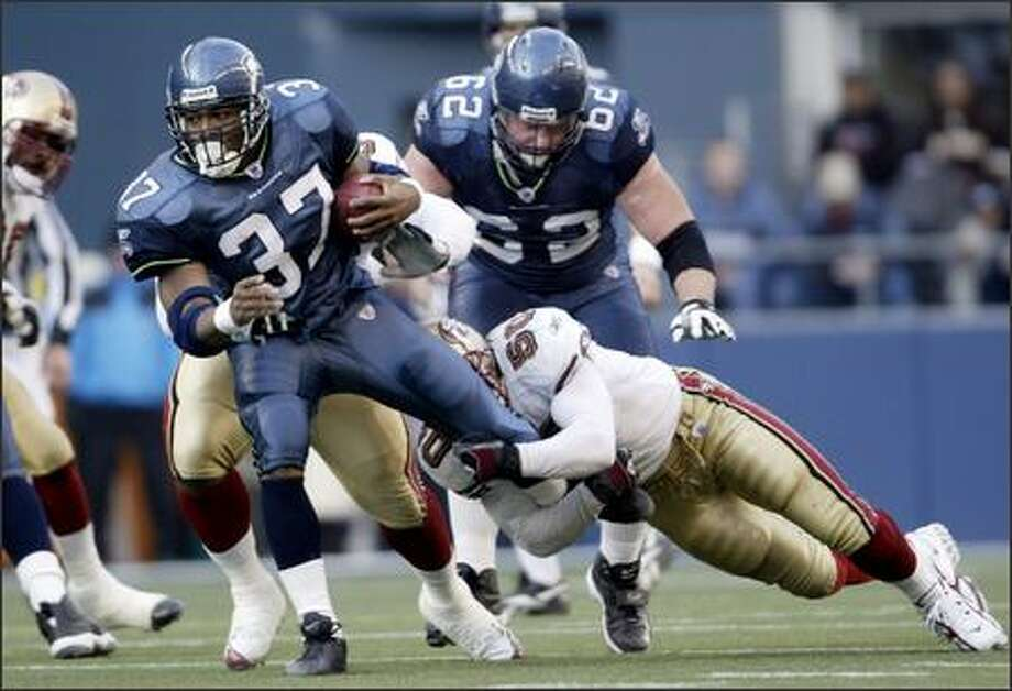 Shaun Alexander runs for nine of his 108 yards before being pulled down by 49ers linebacker Derek Smith in the second quarter. Photo: Dan DeLong/Seattle Post-Intelligencer