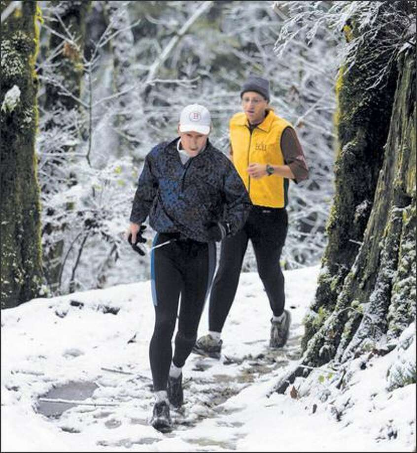 Brent Spilsbury of Shoreline and Carl Kadie of Bellevue, members of the Eastside Runners, jog snow-covered paths recently at Redmond Watershed Preserve. Photo: JIM BRYANT/P-I