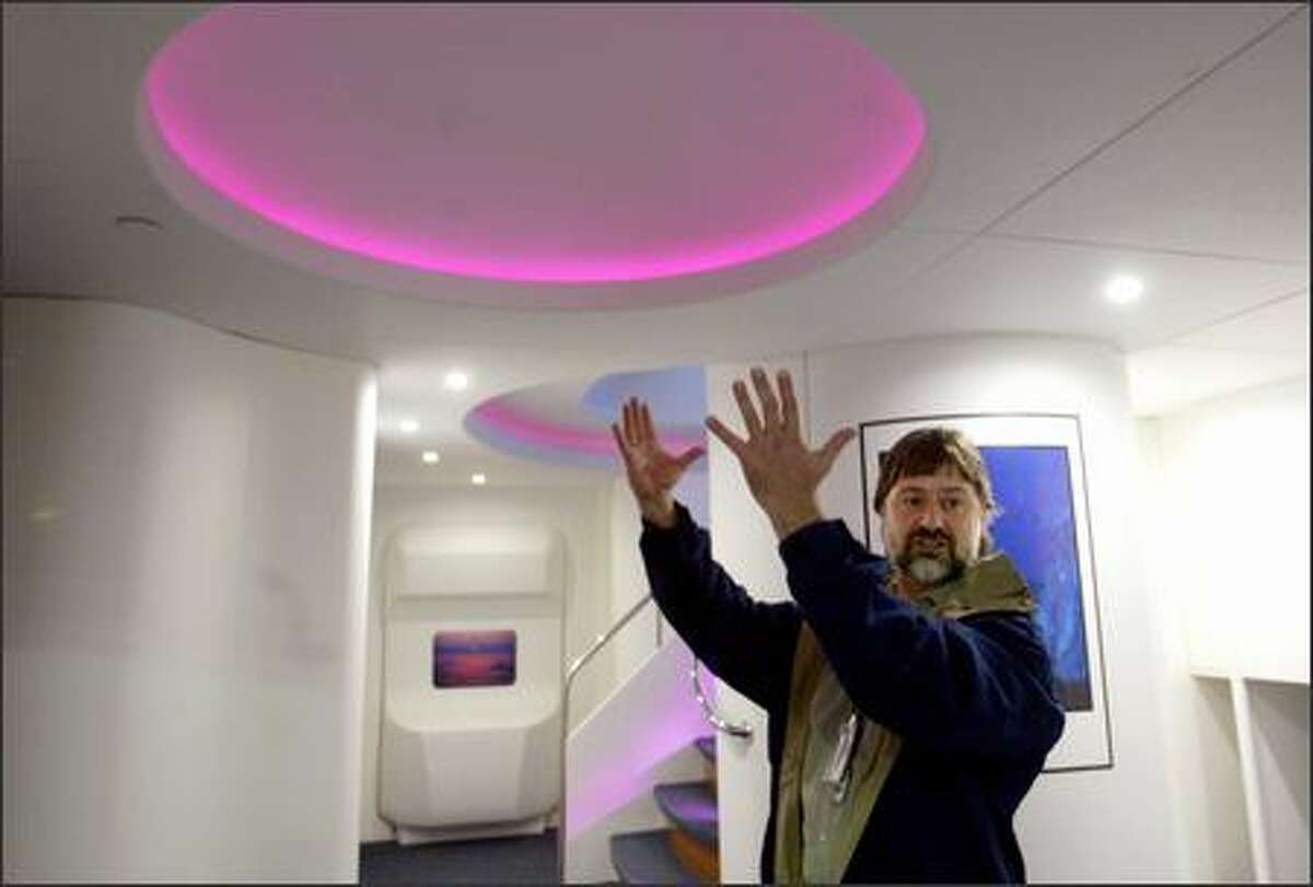 """Boeing's new jumbo jet 747-8 will be offered to customers with sky bunks above the main deck for passengers to sleep in during long flights, and a new interior, including a redesigned entrance into the plane at door No. 2. Roy Eggink, Boeing's chief engineer for 747 product development, shows off this new entryway, featuring a skylight and """"mood lighting."""" View a gallery of photos of the 747-8 interior."""