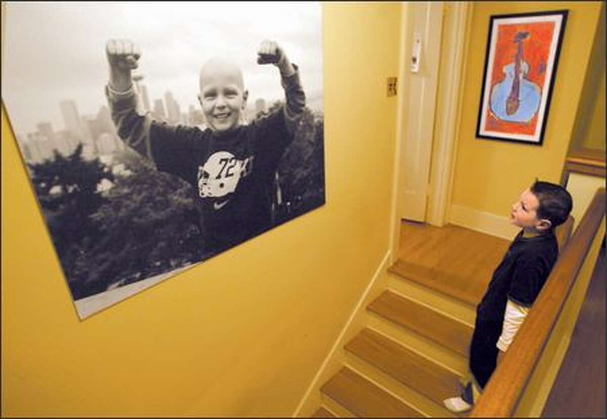 Max Hanson, who is recovering from brain cancer, gazes at a photograph taken by his mother after his final chemotherapy treatment. The photo shows him holding his arms up like a triumphant prizefighter, dwarfing the Seattle skyline behind him.