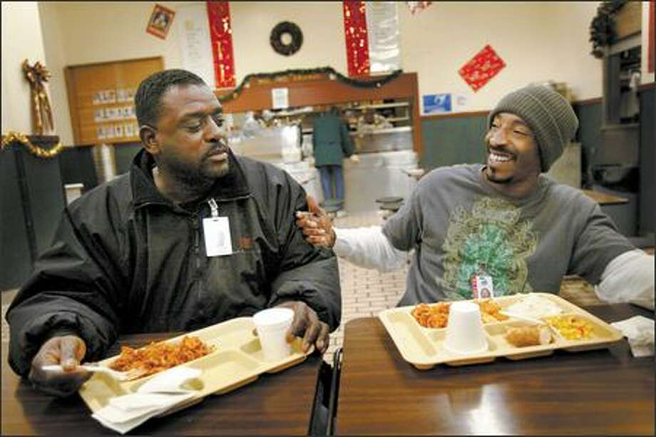 Thomas Turner, left, takes a ribbing from Tyrone Drake as they share a meal Thursday at the Union Gospel Mission in downtown Seattle. In September, the charity received $250,000 less in donations than the same period a year ago. For the mission, that equates to 136,612 fewer meals. Photo: Joshua Trujillo/Seattle Post-Intelligencer
