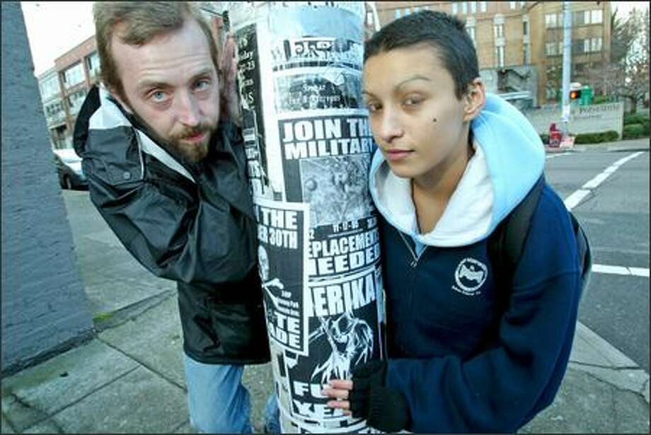 Thomas Hays and Soledad Picon stand next to posters that protest the war in Iraq that someone has attached to a metal pole on Broadway. Hays designed the posters and made them available on his Web site, along with a recipe for glue made with flour and water. Picon helped him translate the posters into Spanish. Photo: GRANT M. HALLER/P-I