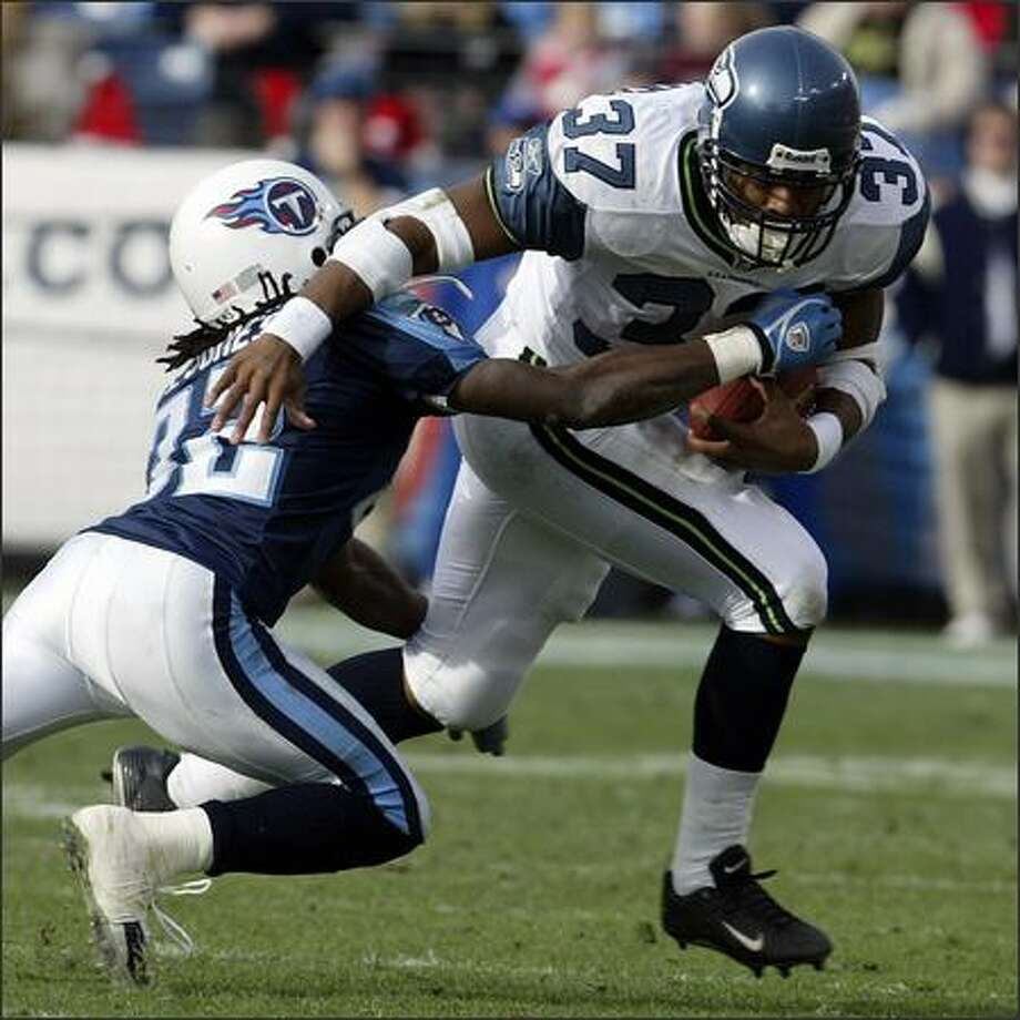 Shaun Alexander rips away from Pacman Jones. Alexander had 172 yards, breaking the 100-yard mark for the 10th time this season. Photo: Mike Urban/Seattle Post-Intelligencer