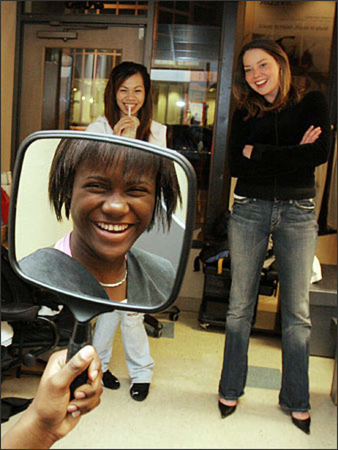 Chiquita Wright checks out her new hairstyle at Seattle's Etherea Salon.Spa as mentor Angela Petlow, right, and friend Tina Nguyen watch. Stylist Charles Fox donated his services. Photo: Meryl Schenker/Seattle Post-Intelligencer
