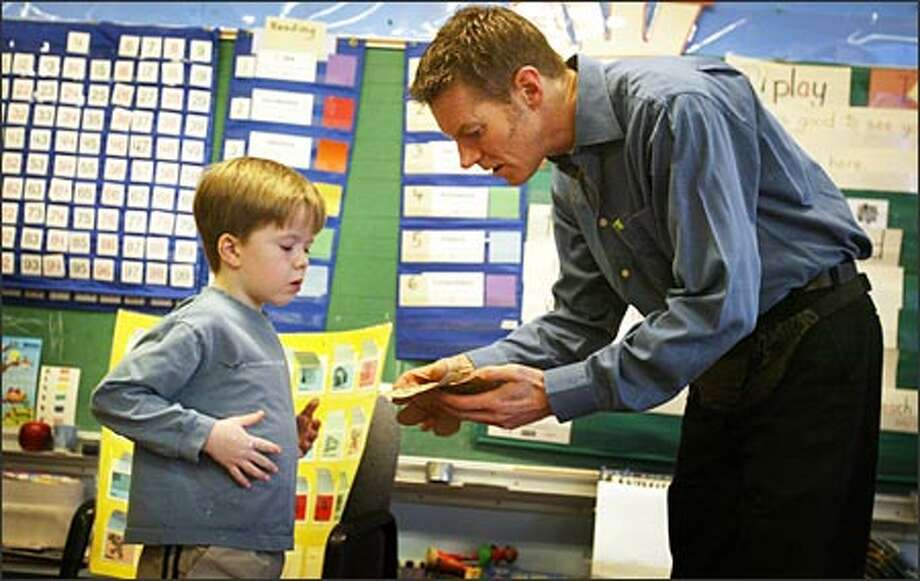 Kevin Gallagher helps kindergartner Austin Armstrong at Sacajawea Elementary. In Seattle, about 20 percent of elementary school teachers are men. Photo: Joshua Trujillo/Seattle Post-Intelligencer