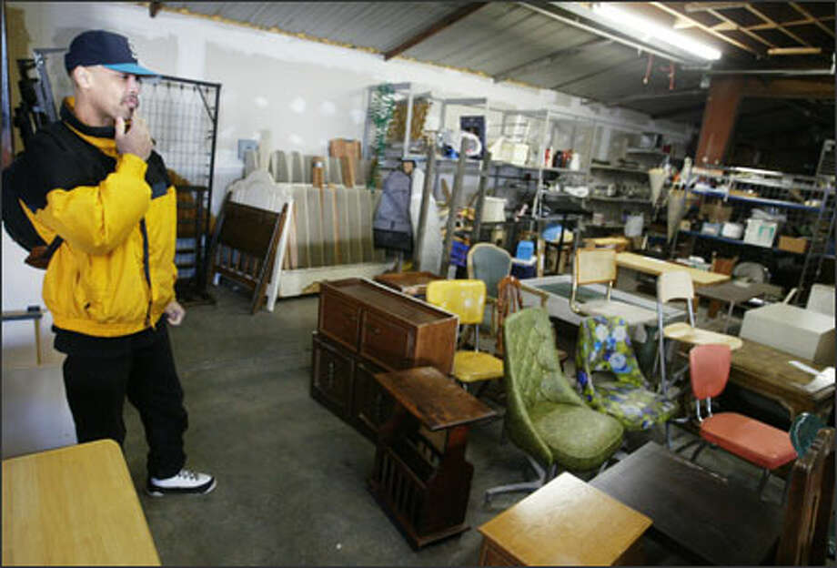 """Derrick Smith, who is furnishing his first apartment after five years of street life, checks out the furniture at The Sharehouse. """"I'm really grateful for this,"""" he says. Photo: Scott Eklund/Seattle Post-Intelligencer"""