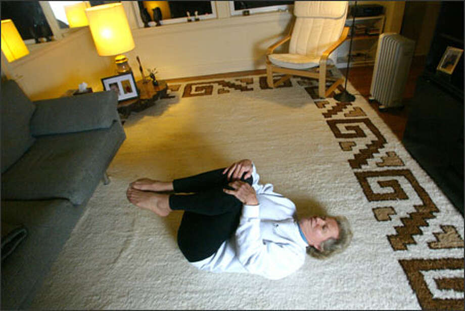 """""""The effect of these yoga classes on my back pain was incredible,"""" says Susana Schuarzberg, practicing a pose in her apartment. Photo: Karen Ducey/Seattle Post-Intelligencer / Karen Ducey"""