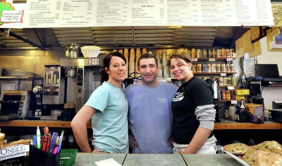Patrick O'Neil stands with employees Mandy Conner, left, and Meg Helbig inside Patrick O'Neil's Sandwich & Coffee Bar in Bethel, Friday, March 18, 2011. Photo: Michael Duffy / The News-Times