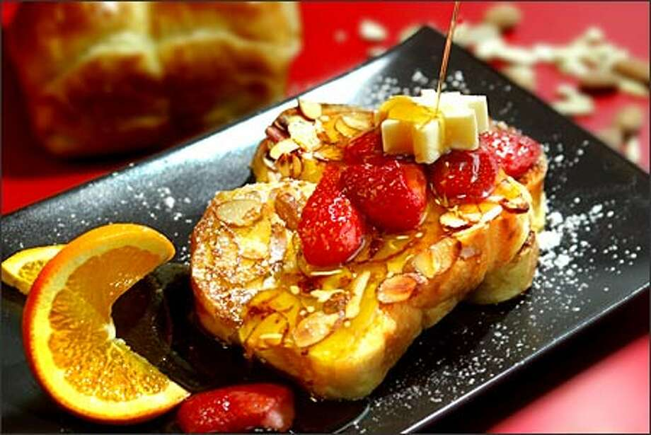 "Pain Perdu from ""Barefoot in Paris"" is served here with frozen strawberries, powdered sugar and maple syrup. Brioche was dipped in batter and sliced almonds. Photo: Scott Eklund/Seattle Post-Intelligencer"
