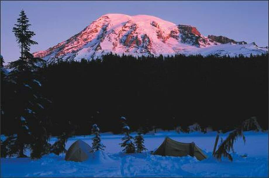 Alpenglow on Mount Rainier lights a camp at Reflection Lakes. Photo: ANDREW NICHOLLS