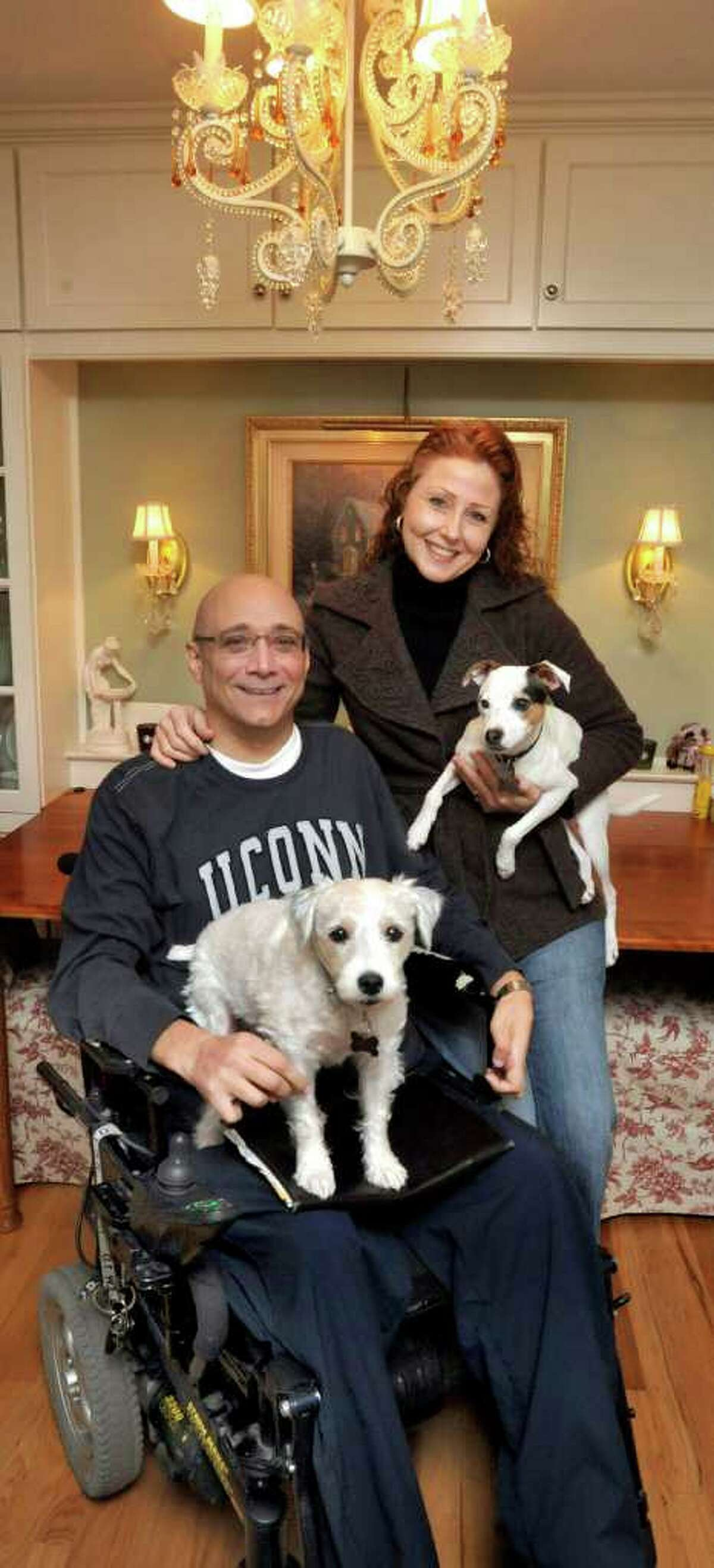 Gary and Keri Baldelli pose with their dogs, Jenni, left and Bailey, right, in their Danbury home, Friday, Jan. 7, 2011.