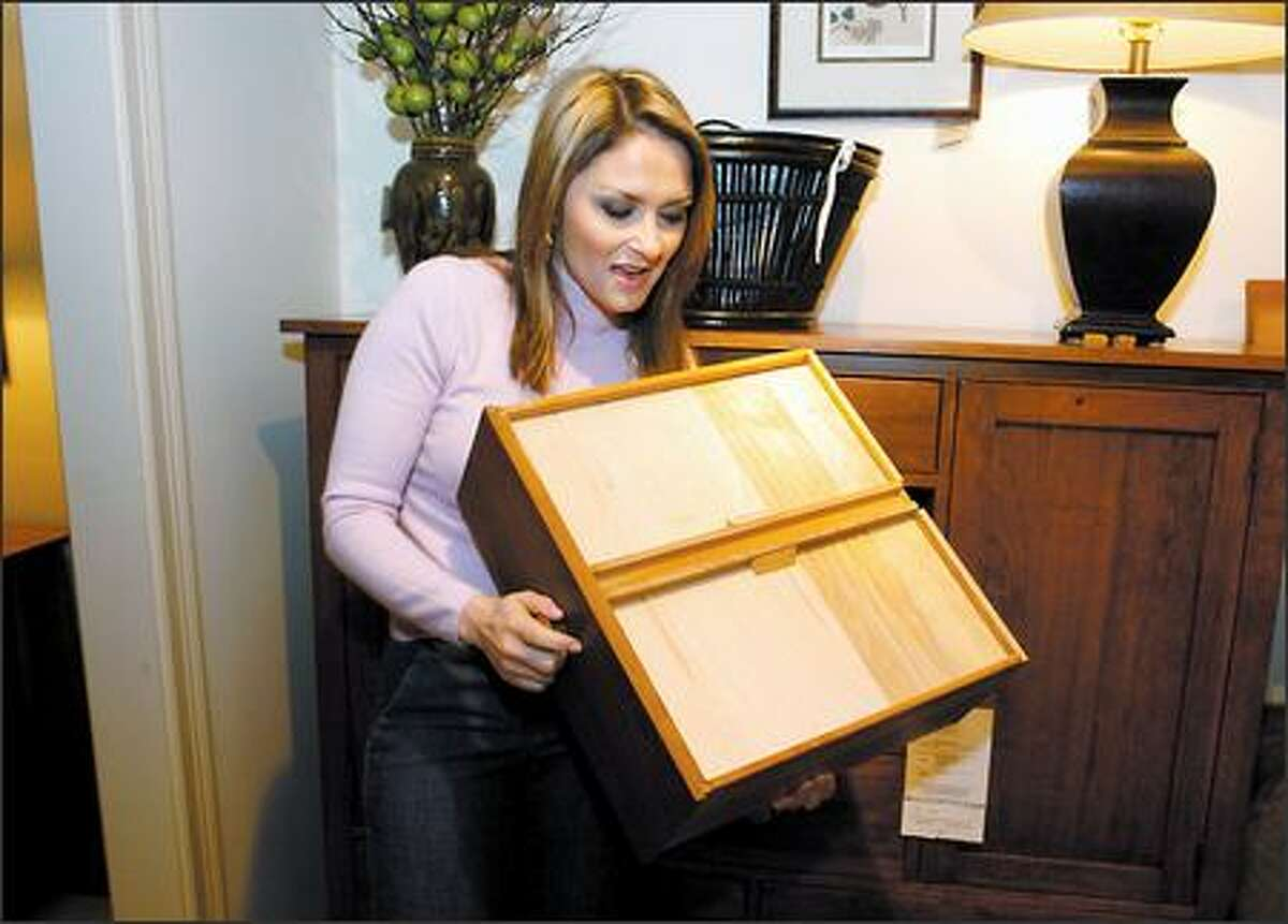 Furniture critique, author and shopper Jennifer Litwin examines the construction and drawer glides of a cherry cabinet at the Southcenter Ethan Allen during her visit with local media December 5, 2005. (Steve Shelton Images)