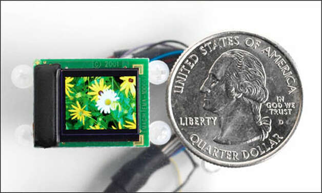 A close-up of the display component of the new wearable display for video iPods by eMagin Corp., compared with the size of a quarter. Photo: EMagin Corp. / EMAGIN CORPORATION
