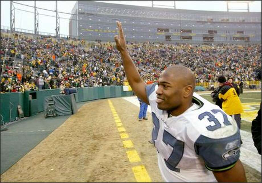 Shaun Alexander acknowledges the crowd after breaking the single-season record for touchdowns with his 28th. He gained 73 yards to claim the rushing title with 1,880 yards. Photo: Scott Eklund/Seattle Post-Intelligencer