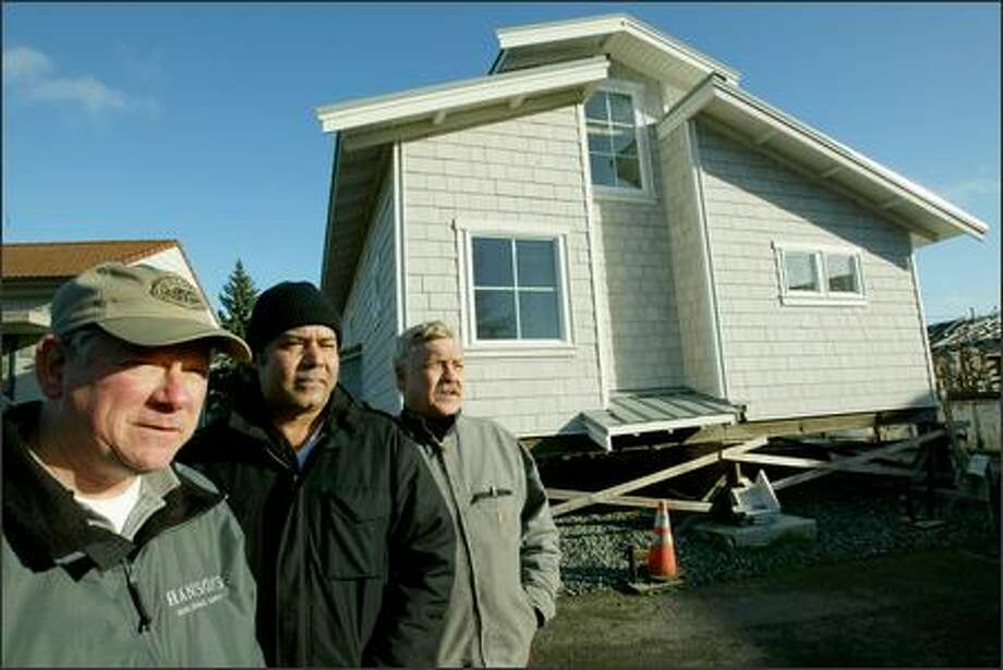 Carpentry instructors Frank Mestemacher, left, and Randy Jones, right, stand with Raj Parashar, who owns the home built by students in the parking lot of the Wood Construction Center, a program offered through Seattle Central Community College. The modular home will be taken apart and shipped to Prosser by truck. Photo: Grant M. Haller/Seattle Post-Intelligencer