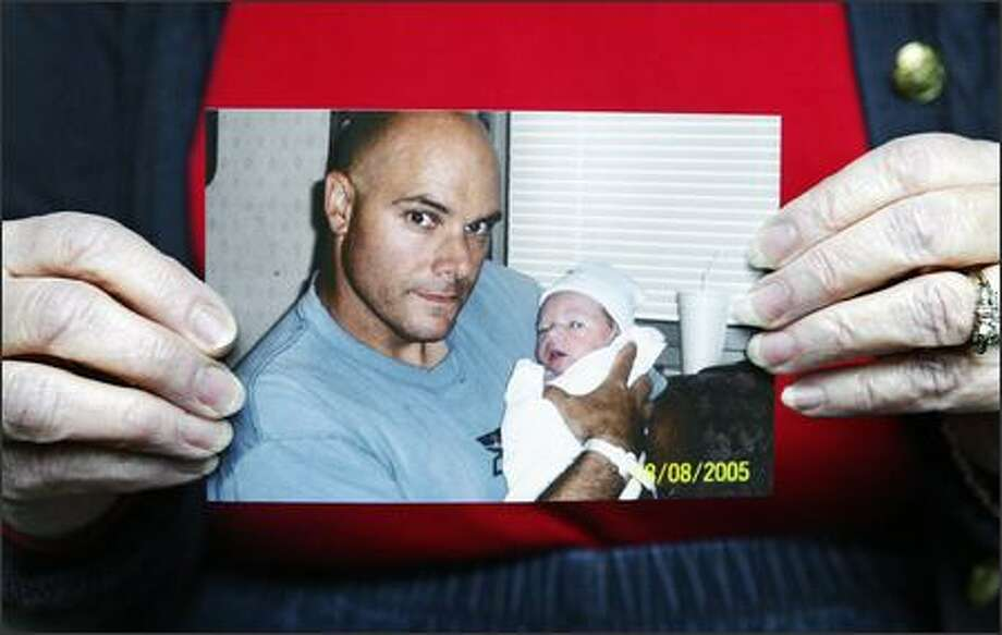 A picture of Chris Van Der Horn holding his newborn son, Liam, this past August is held by his mother, Nancy Van Der Horn of Bellevue. Army Staff Sgt. Chris Van Der Hor, 37, who was raised in Beaux Arts Village, was killed Sunday in As Sinia, Iraq. Photo: Gilbert W. Arias/Seattle Post-Intelligencer