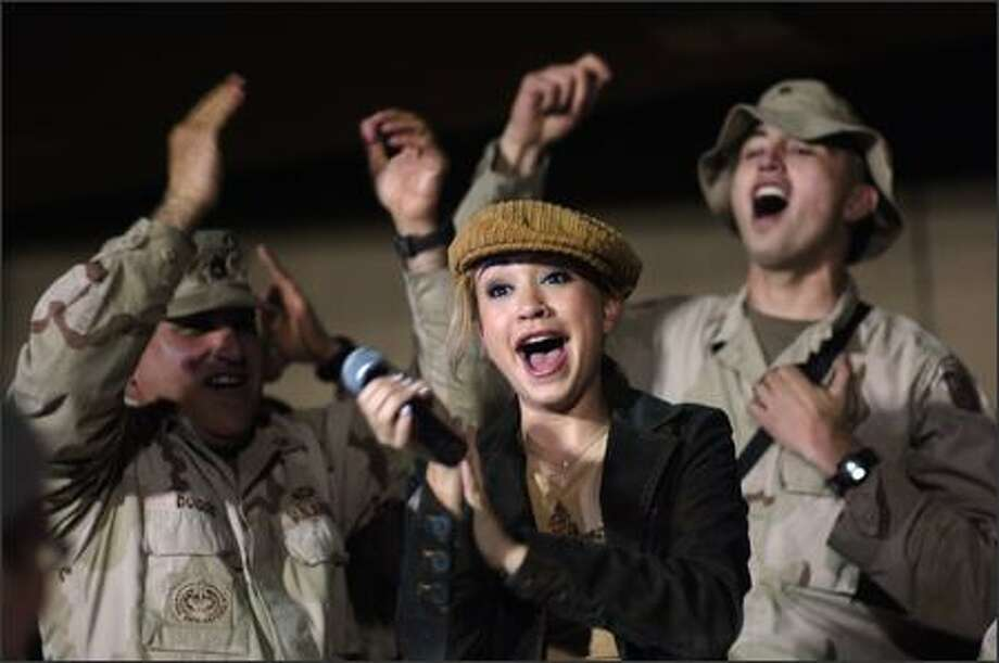 """After all the U.S. troops have to put up with in hazardous duties overseas these days, is this the best the country can offer in gratitude? A concert by the runner-up on """"American Idol?"""" Indeed it is, as groovin' Diana DeGarmo demonstrated as headliner in a weeklong concert gig for troops overseas sponsored by the USO. Photo: AP"""