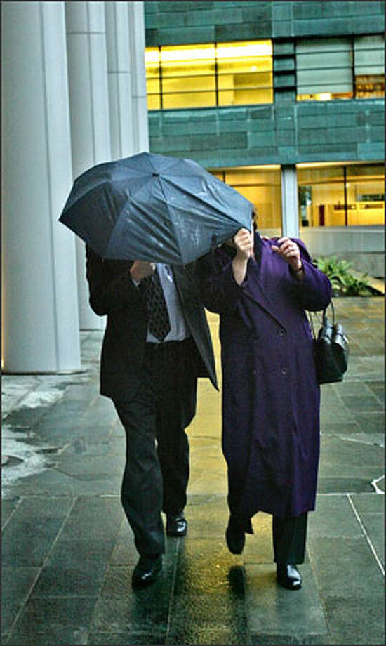 Wade and Laura Cook hide behind an umbrella on Thursday after leaving U.S. District Court in Seattle. Photo: Grant M. Haller/Seattle Post-Intelligencer