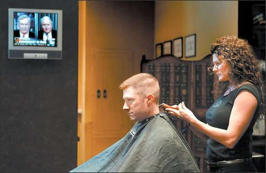 """During its two years in a downtown office building, Capelli's Gentlemen's Barbershop has built a loyal following, including Michael Fall, here getting a cut from Capelli's owner Simone Loban. """"This is their place. ... It screams them,"""" Loban says of her shop's masculine ambience. Photo: SCOTT EKLUND/P-I"""