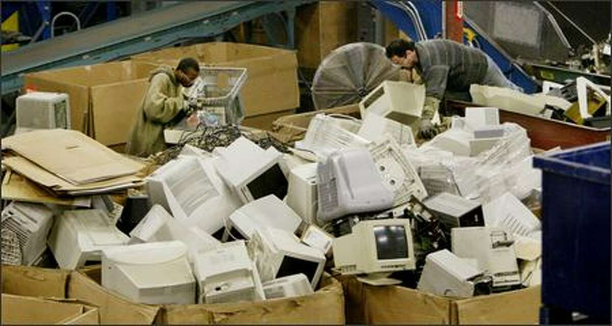 Vernon Cummings, left, and Shane Worthen, employees at Total Reclaim in Seattle, disassemble computer monitors. The different materials must be separated before they can be recycled.