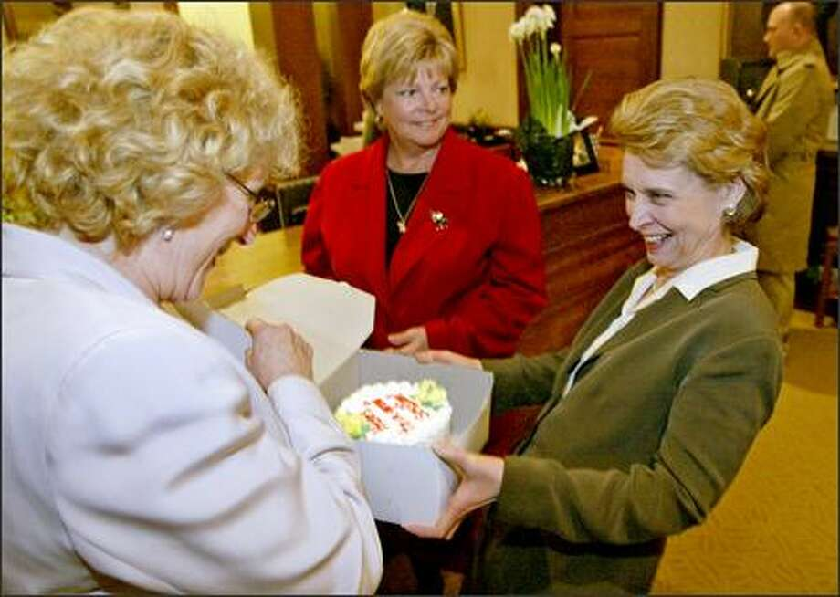 "Reps. Mary Lou Dickerson, D-Seattle, and Beverly Woods, R-Poulsbo, give Gov. Christine Gregoire a cake Monday that reads, ""Here's to a Great Session."" Photo: Mike Urban/Seattle Post-Intelligencer"