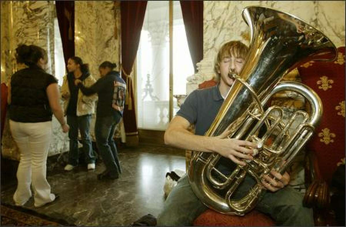 In the Capitol Building Reception Room, Jens Peterson of Lakes High School in Lakewood works on his tuba solo while, in the background, fellow students practice their hip-hop dance moves for the opening ceremonies of the 2006 legislative session in Olympia.