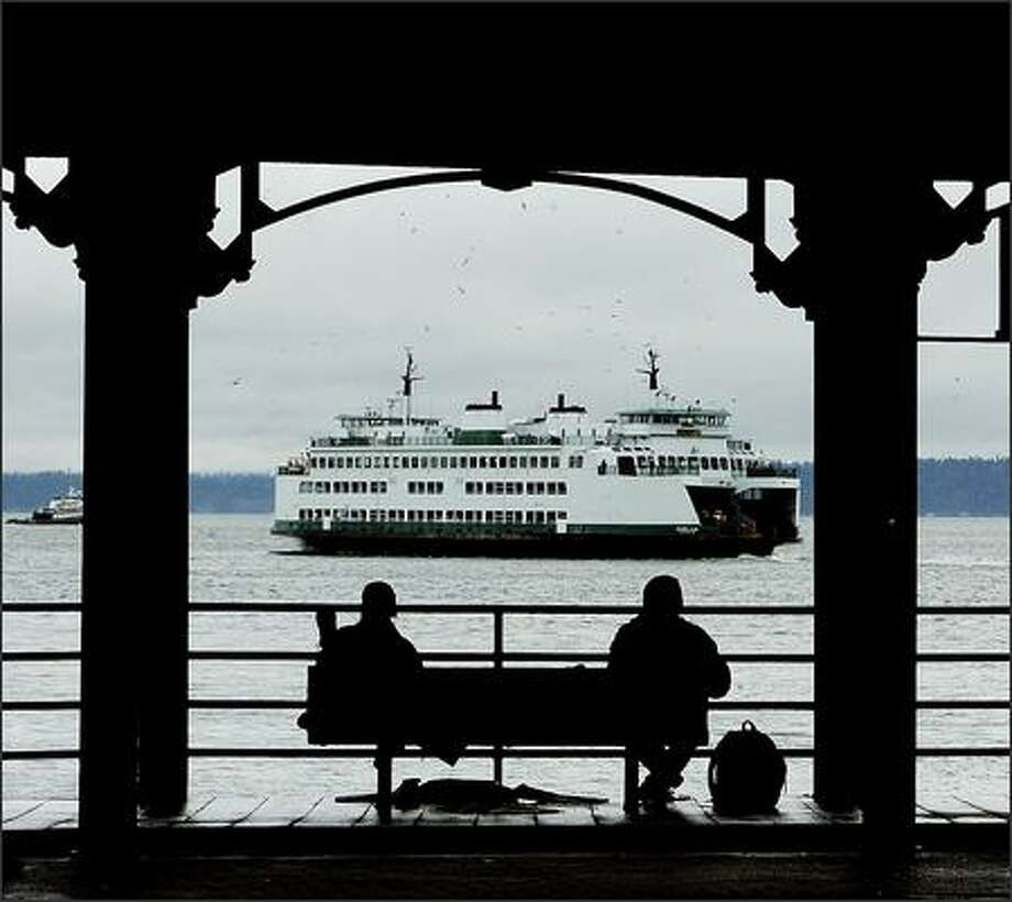Two men sit Monday at the dilapidated Washington Street Public Boat Landing at the waterfront as a ferry departs for Bremerton. Photo: Dan DeLong/Seattle Post-Intelligencer