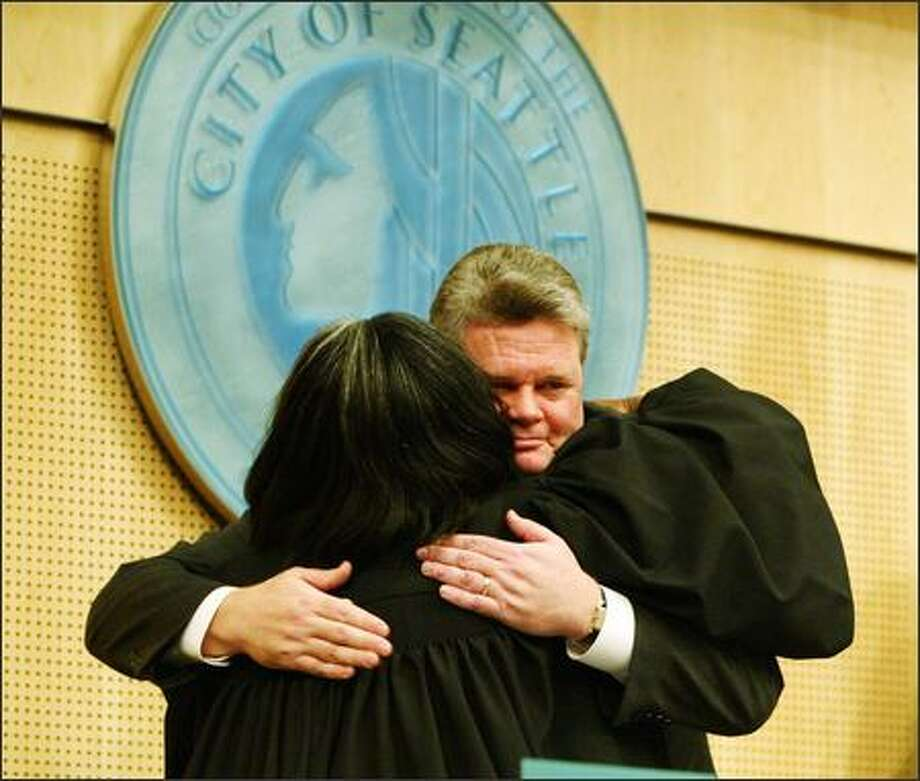 Municipal Court Judge Edsonya Charles gets a hug from Mayor Greg Nickels after she administered the oath of office to the mayor on Monday. In a brief speech, Nickels said that during the next four years in office, he will focus on transportation, affordable housing and education issues. Photo: Gilbert W. Arias/Seattle Post-Intelligencer
