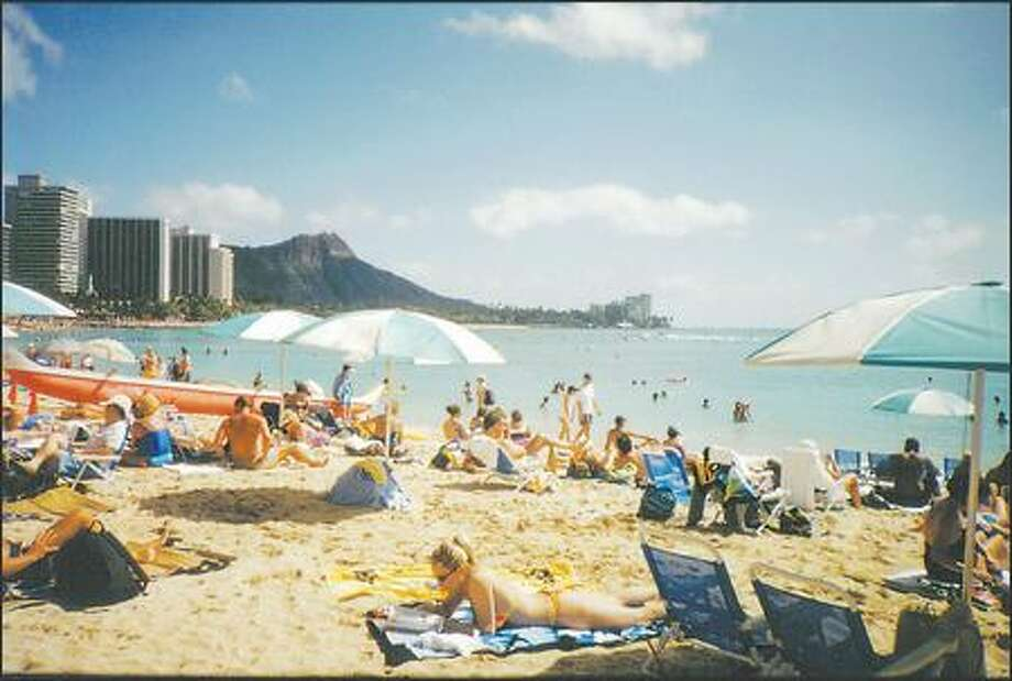 While Waikiki is famous for fine sand and gentle surf, it's almost too crowded to find a comfy spot. Photo: ANNIE PALOVCIK