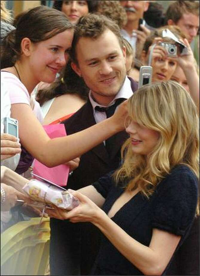 """Aussie hunkster Heath Ledger and Michelle Williams, his co-habitor and co-star, greet fans at the Australian premiere of """"Brokeback Mountain"""" Tuesday in Melbourne. The gay caballero flick scored three Critics' Choice Awards Monday, including best pic, best director and best supporting actress for Williams. Photo: AP"""