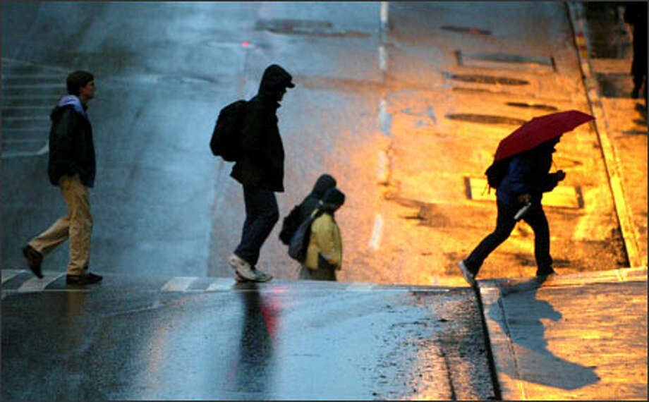 """Pedestrians slosh across a street Tuesday in downtown Seattle. A State Patrol trooper grumbled about the long spell of wet weather, """"This is getting dreary; I need sun!"""" Photo: Karen Ducey/Seattle Post-Intelligencer"""