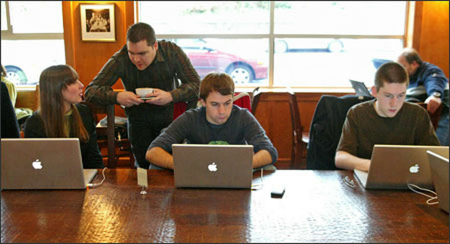 "Wil Shipley, second from left, ""chief monster"" for Delicious Monster, talks to employees Rachel Wallace, left to right, Lucas Newman and Drew Hamlin at Zoka coffee shop. Photo: Gilbert W. Arias/Seattle Post-Intelligencer / Seattle P-I"