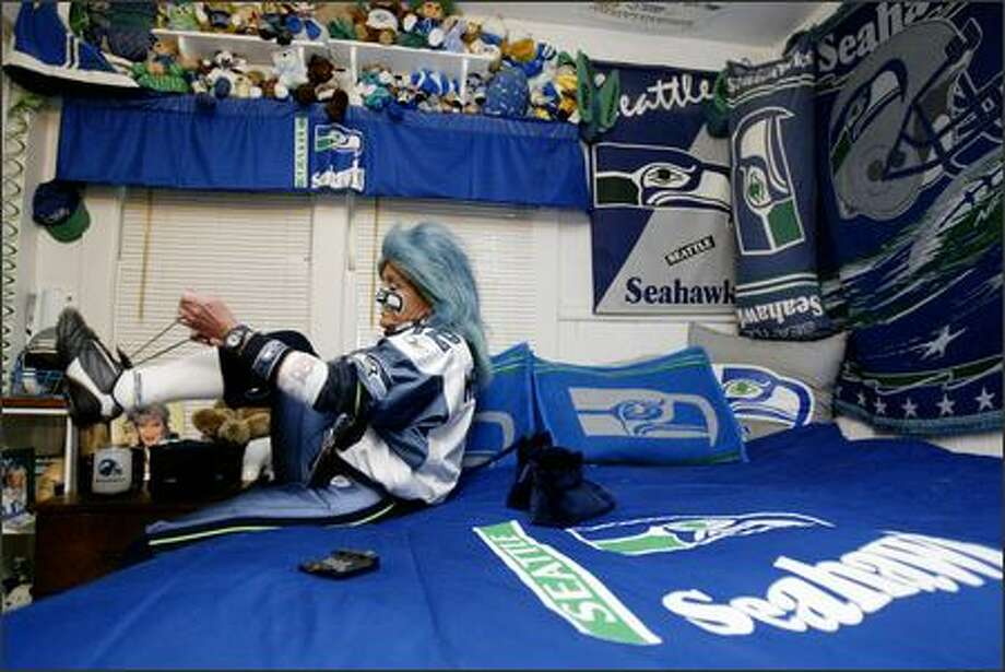 In the bedroom of her Auburn home, Mrs. Seahawk, DeDe Schumaier, ties her shoes before heading to Seattle's Nov. 13 game against St. Louis. Photo: Dan DeLong/Seattle Post-Intelligencer