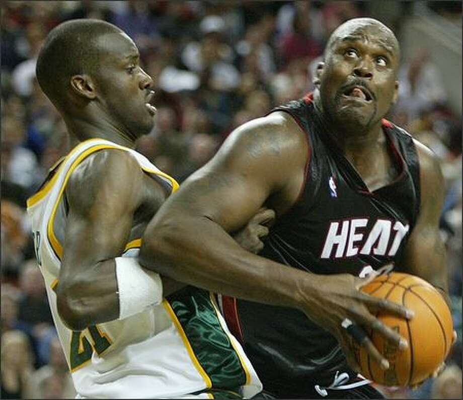 Shaquille O'Neal muscles inside against Sonics rookie Johan Petro. O'Neal scored 16 points in 23 minutes. Dwyane Wade had a triple-double for Miami. Photo: Grant M. Haller/Seattle Post-Intelligencer