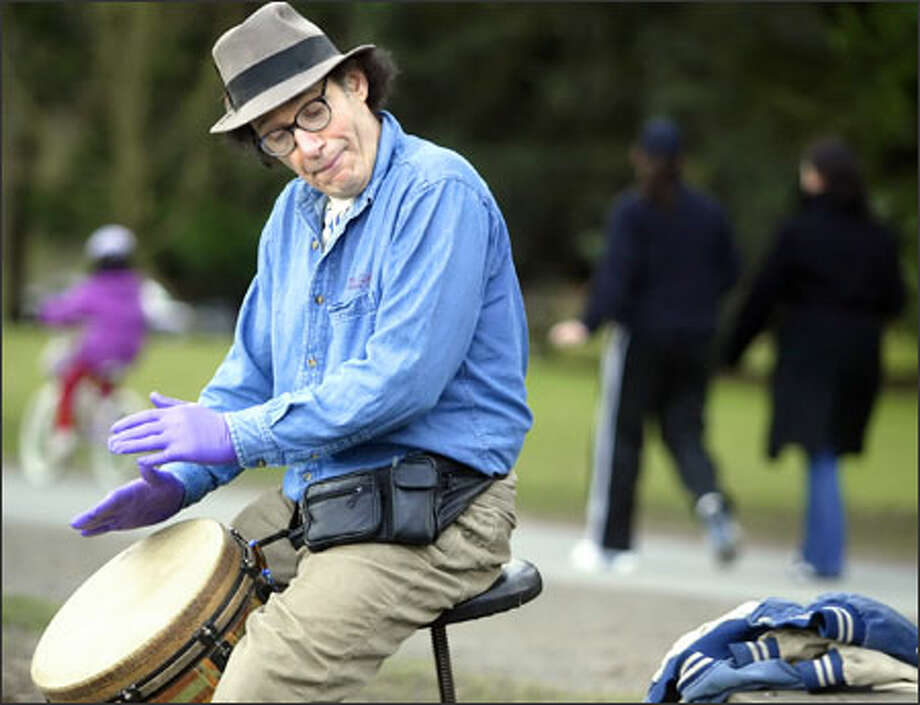 Clear skies Sunday over Green Lake in Seattle lured out bicyclists, joggers -- and Ed Sullivan. His latex gloves change the drums' sound. Photo: Jim Bryant/Seattle Post-Intelligencer