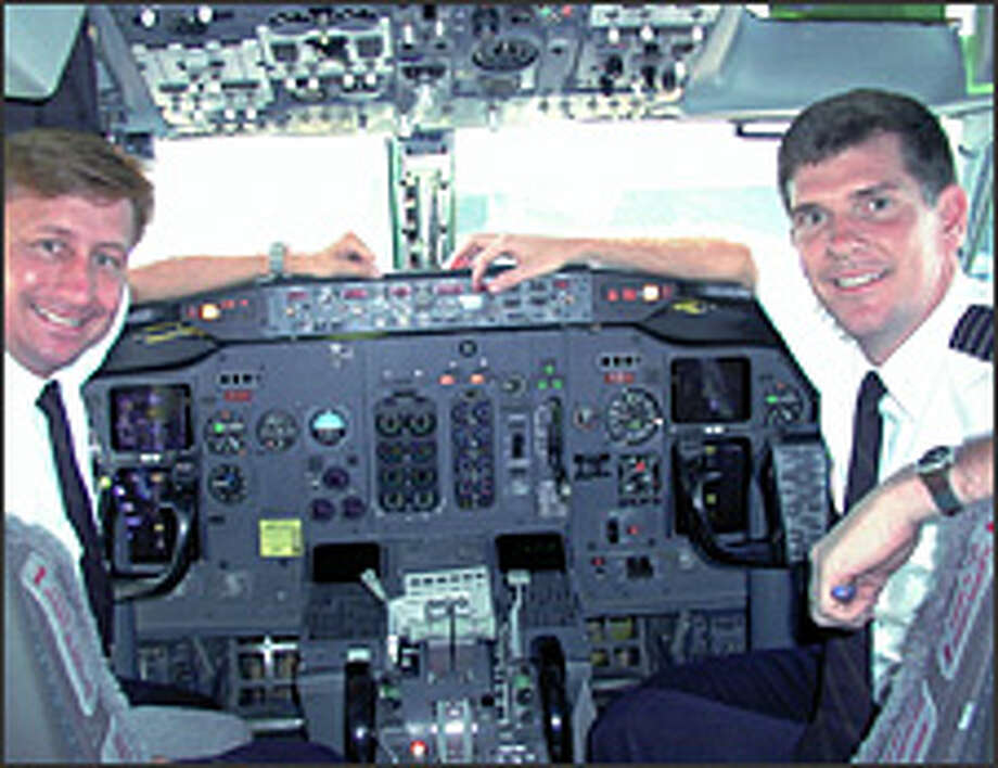 Steve Fulton, right, and Hal Andersen smile from the cockpit of an Alaska Airlines 737-400 in 2002. As a pilot for the airline in the 1990s, Fulton helped pioneer procedures for using the satellite-based navigation system known as Required Navigation Performance.