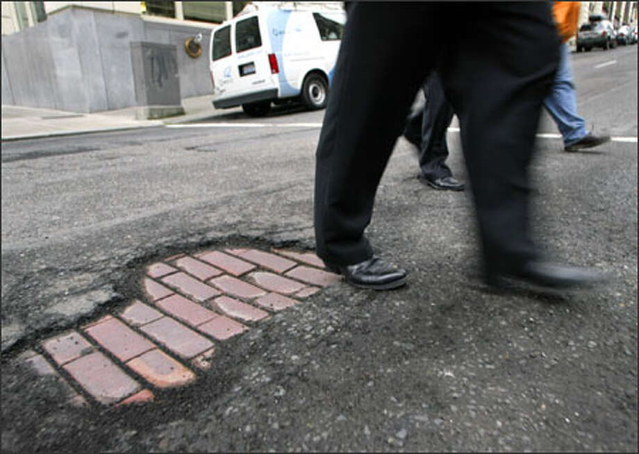 Pedestrians and motorists navigate around a pothole at the intersection of Cherry Street and Second Avenue in downtown Seattle. Photo: Jim Bryant/Seattle Post-Intelligencer / SEATTLE POST-INTELLIGENCER