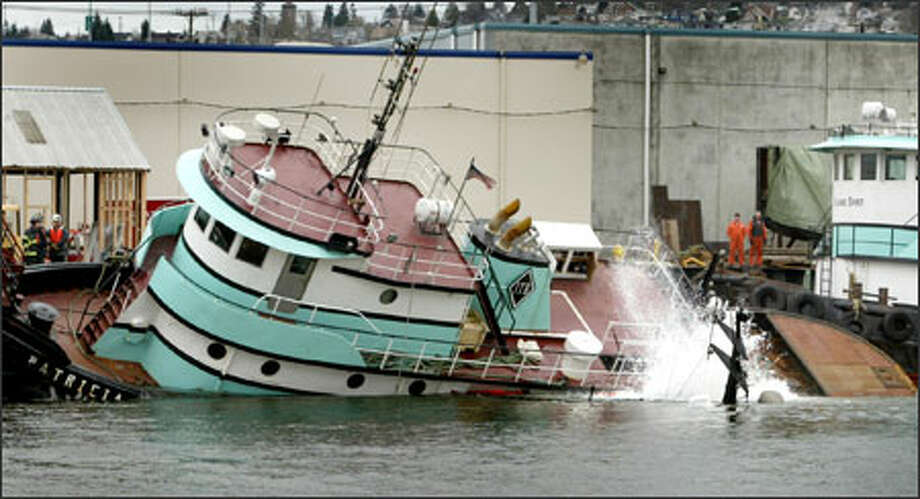 Recovery workers watch helplessly Sunday as the tugboat Patricia S lists mightily and is nearly pulled to the bottom of Elliott Bay by the sinking tugboat Island Brave. The Patricia S was moored to the dock, and the Island Brave was tied to the other tug. The Island Brave's mast is just visible by the splash of water at right. Photo: Joshua Trujillo/Seattle Post-Intelligencer / Seattle Post-Intelligencer