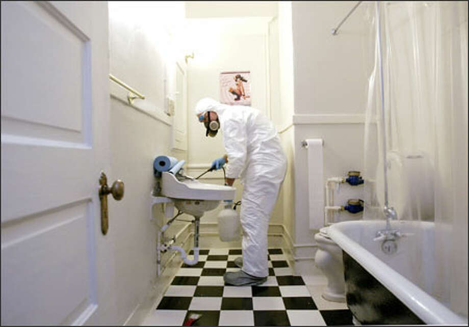 In a downtown Seattle apartment, site of a recent suicide, Crime Scene Cleaners franchise co-owner Richard Fleming wears protective gear as he finishes cleaning up. Photo: Dan DeLong/Seattle Post-Intelligencer