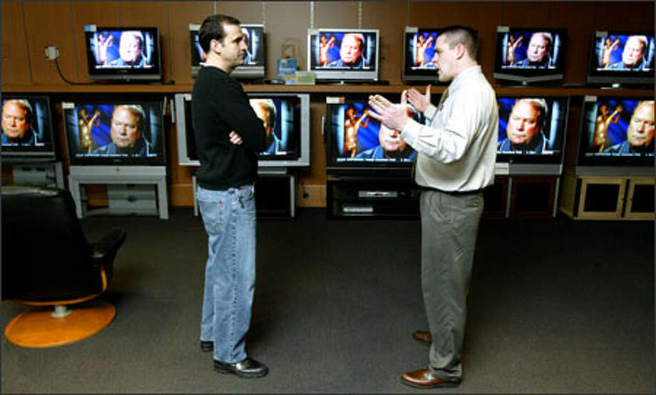 Magnolia Audio Video's Ted Wendt, right, explains the differences among big-screen televisions to customer Robert Todd at the company's Roosevelt store Tuesday. Photo: Mike Urban/Seattle Post-Intelligencer / Seattle Post-Intelligencer