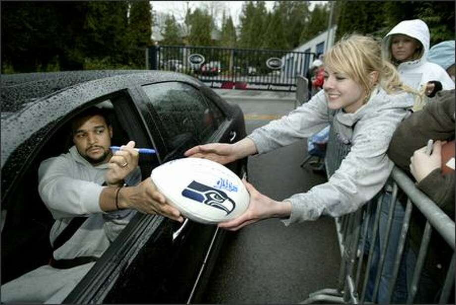 Seahawks safety Michael Boulware autographs a football for Alexandria Griffin of Vancouver, Wash., after practice Thursday. Photo: Dan DeLong/Seattle Post-Intelligencer