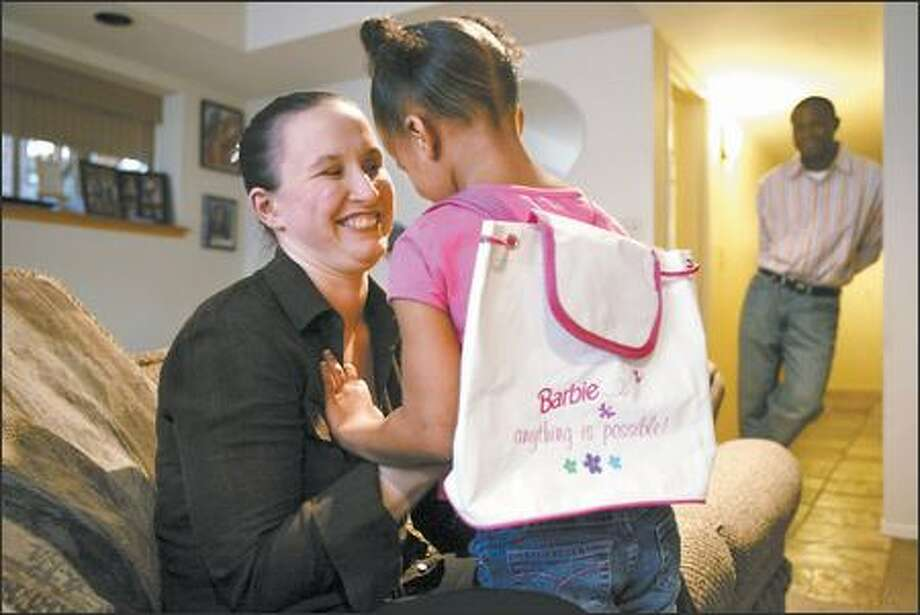 With husband John Hart in the background, Carly Alcombrack plays with her daughter, Jahdai, in their Bellevue home. Jahdai's love for Barbie started the trouble. Photo: MIKE URBAN/P-I