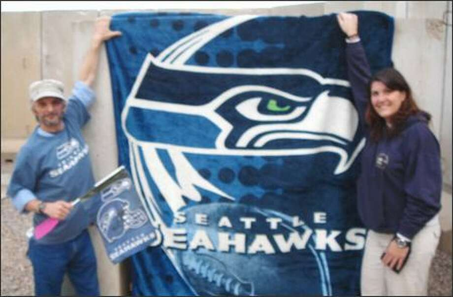 """Jody Lepore, left, and another Seahawks fan, Stacey Pierce, formerly of Puyallup, drape a blanket over one of their """"bunkers"""" when mortar attacks hit. Both work for AFSBn-IZI, Army Material Command at Balad Air Base (Camp Anaconda), Iraq."""