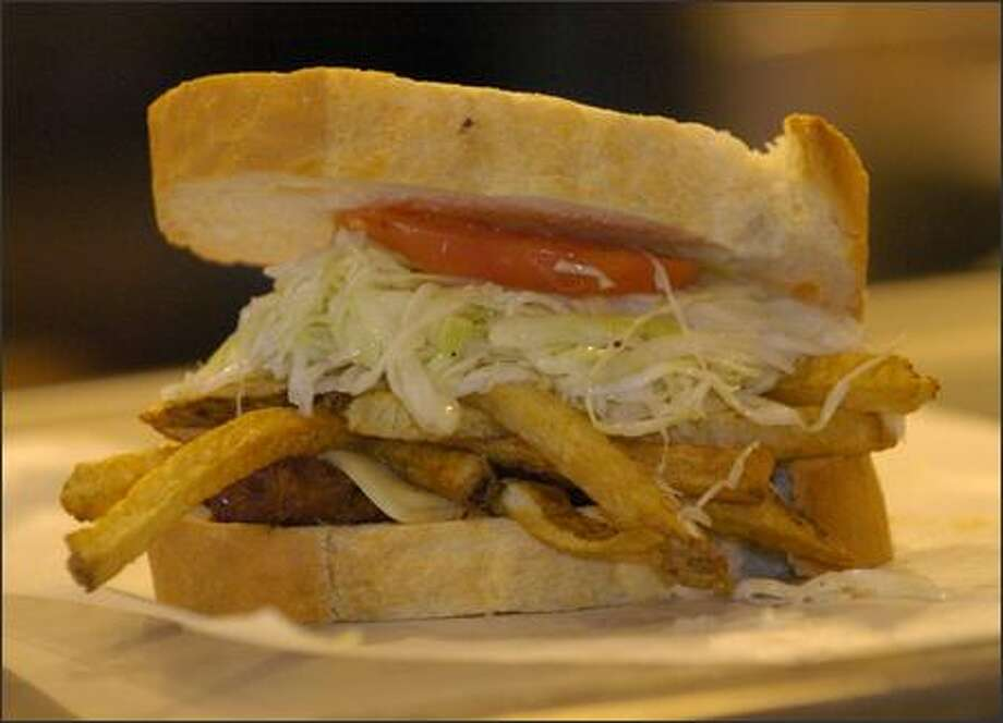 A Primanti Brothers sandwich is a staple of the Pittsburgh (heart) attack. Pile on salami, ham, provolone cheese, vinegar-style cole slaw and french fries. Yes, french fries. Photo: Tony Tye/Pittsburgh Post-Gazette
