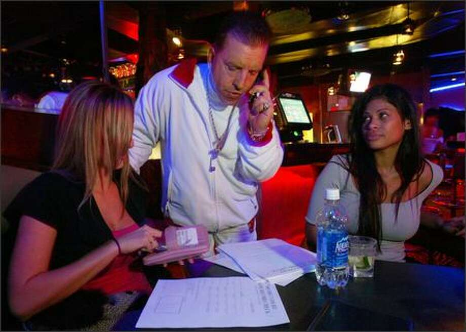 Kristine, left, works on her dancer ID card application at Players, a topless club on 8 Mile Road in Detroit, as agent Kenny Cory conducts business on the phone and Lydia listens. Lydia says she once received a $5,000 tip for a lap dance. Photo: Grant M. Haller/Seattle Post-Intelligencer