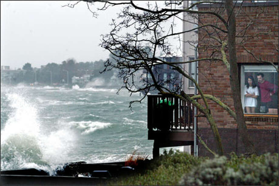 A couple watch as a combination of high tides and strong wind causes waves to crash over the bulkhead of their building on Beach Drive in Alki on Saturday. The wind and rain storm caused power outages throughout the region, and some Seattle City Light customers were still without power Sunday. Photo: Karen Ducey/Seattle Post-Intelligencer