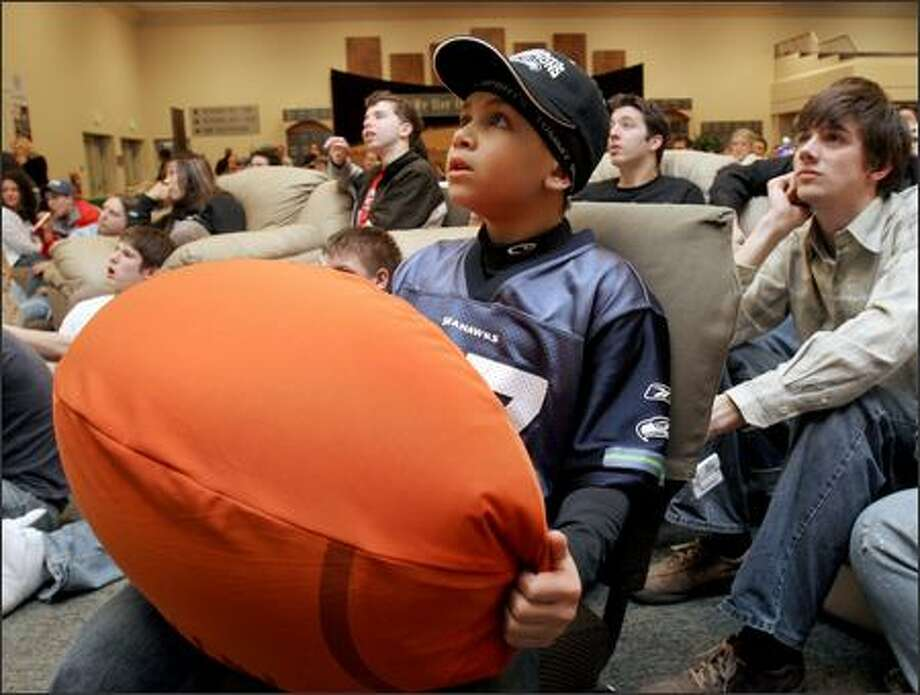 Marquel Ruffin, 9, watches the Super Bowl on a large screen at SeaTac's Christian Faith Church, which Seattle Seahawk Shaun Alexander attends when he's in town. Photo: MERYL SCHENKER/P-I