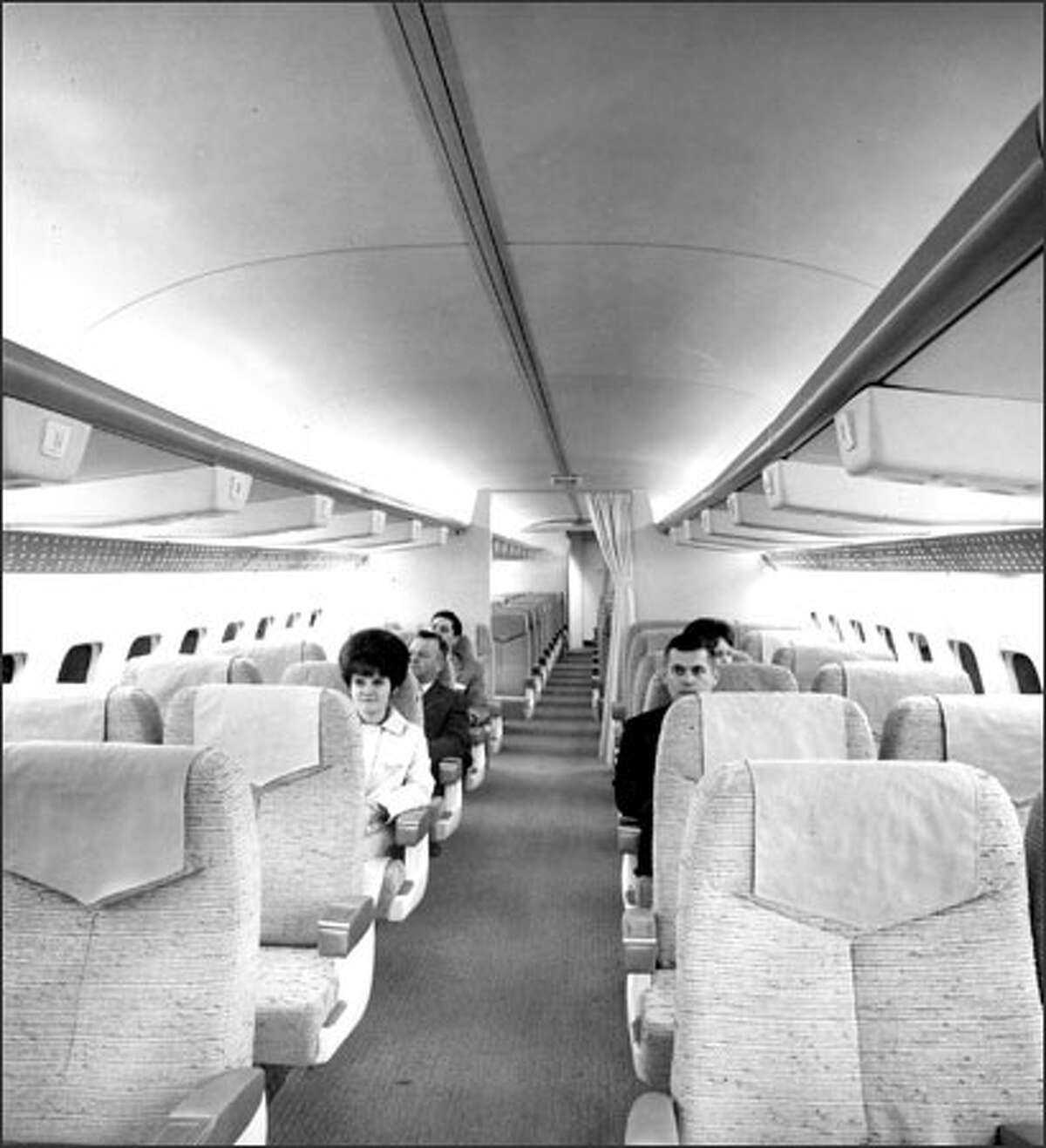 Boeing employees sit in the first-class section of a sales mockup of the 737 jetliner, about a year before the 737's maiden flight.