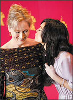 "And now for a little smooch on Valentine's Day from unexpected quarters. Vampy teen queen Lindsay Lohan prepares to plant a smacker on the cheek of classy Meryl Streep at the Berlin Film Festival. The unlikely duo were pumping a film version of ""A Prairie Home Companion"" being shown in Germany's Bear City capital."
